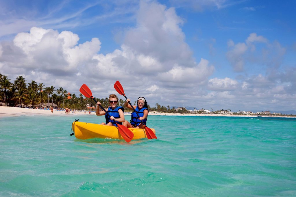 Two women in lifejackets paddling in a yellow boat, punta cana la altagracia dominican republic : Stock Photo