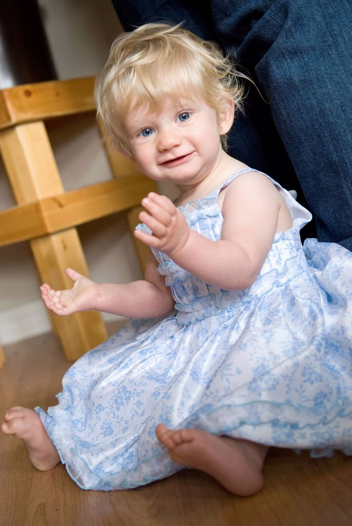 A young girl with blond hair and blue eyes sitting on the floor in a dress, millet alberta canada : Stock Photo