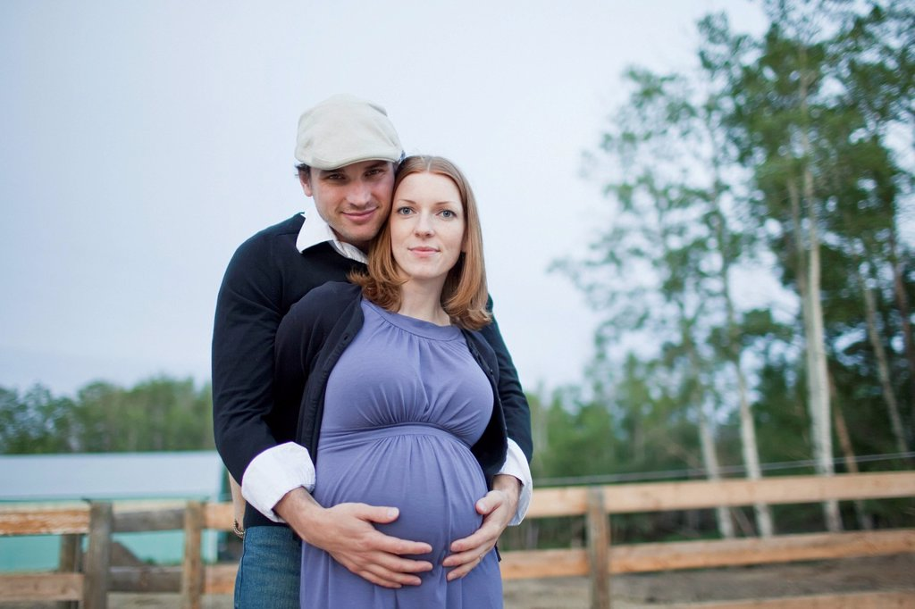 Stock Photo: 1889R-77715 A husband embraces his wife and her pregnant belly, sherwood park alberta canada