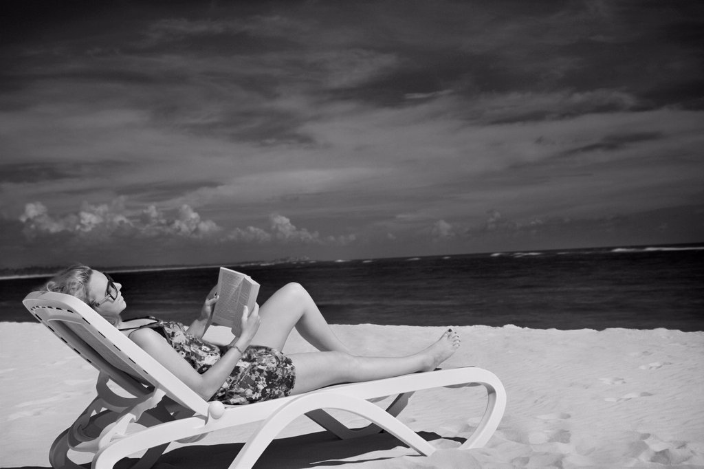 Stock Photo: 1889R-77716 A woman sits reading in a lounge chair on the beach, punta cana la altagracia dominican republic