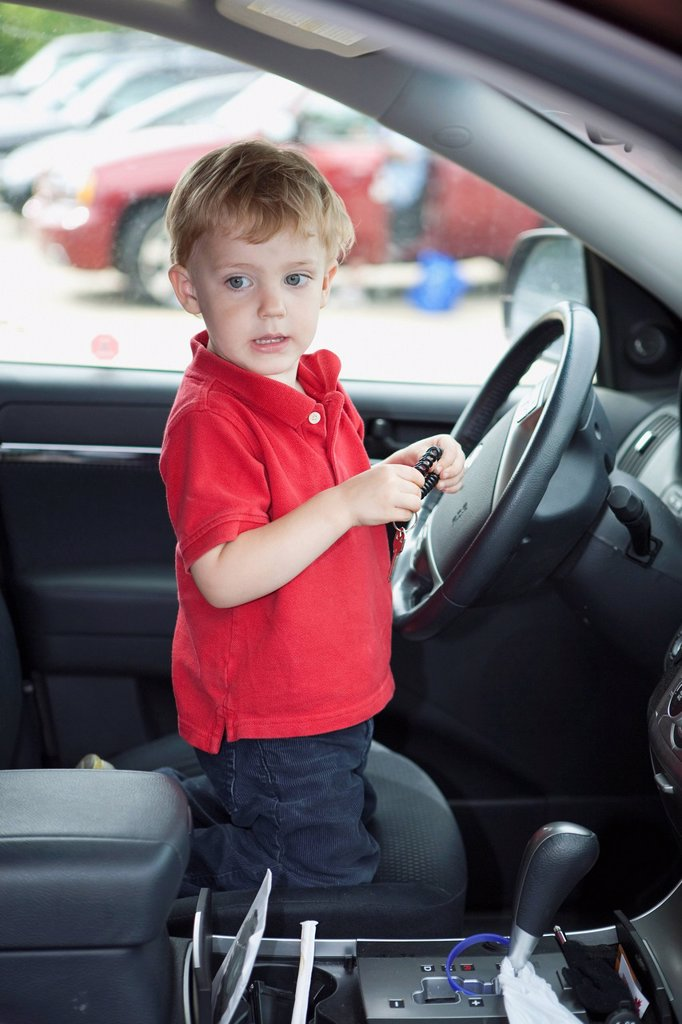 Stock Photo: 1889R-77823 a young boy sits by the steering wheel in the front seat of a car, edmonton, alberta, canada