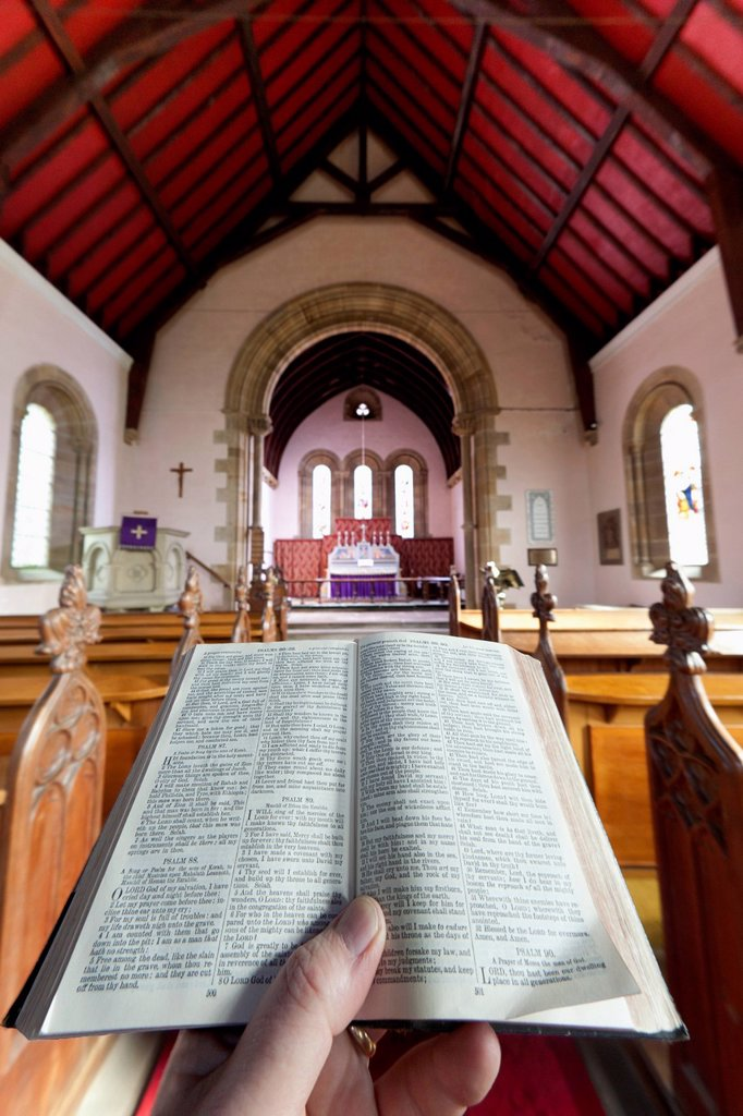 Stock Photo: 1889R-78206 A hand holds a small open bible at the back of a church, howick northumberland england