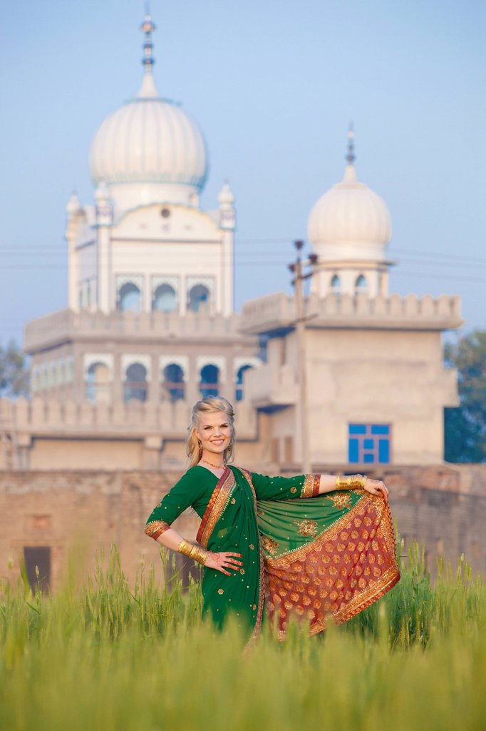 Portrait of a blond woman wearing a sari in a field with a temple in the background, ludhiana punjab india : Stock Photo