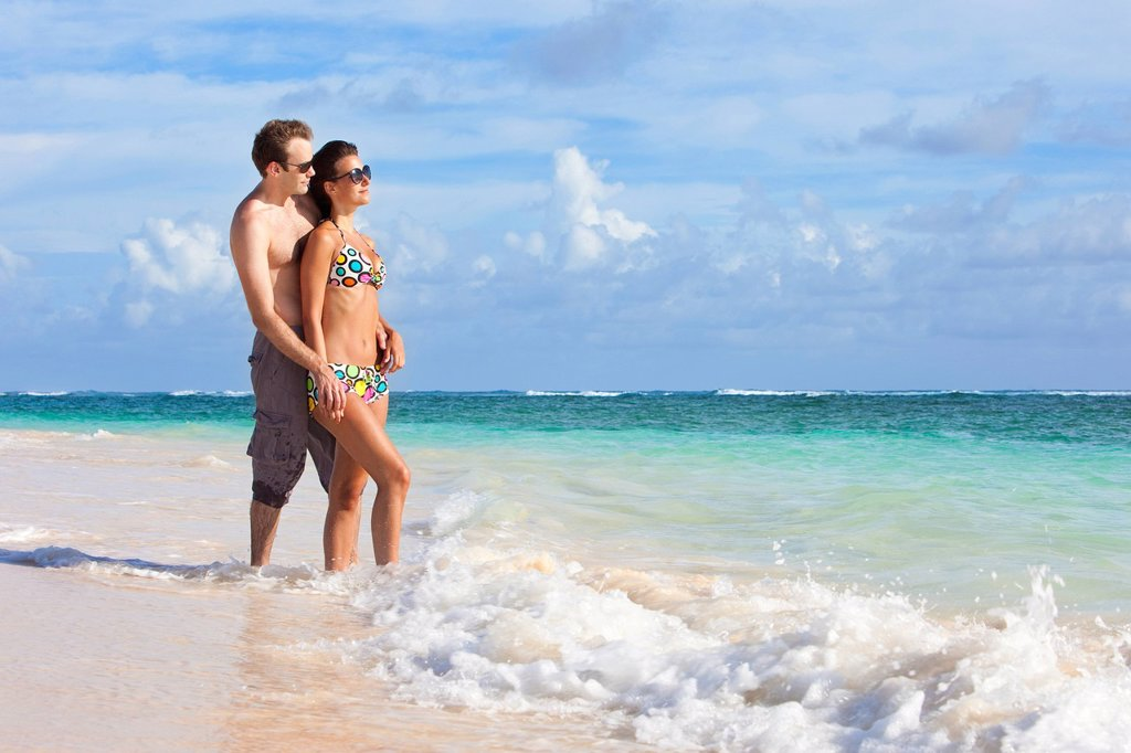 Stock Photo: 1889R-78361 A couple wearing swimsuits stand in the ocean holding hands, punta cana la altagracia dominican republic