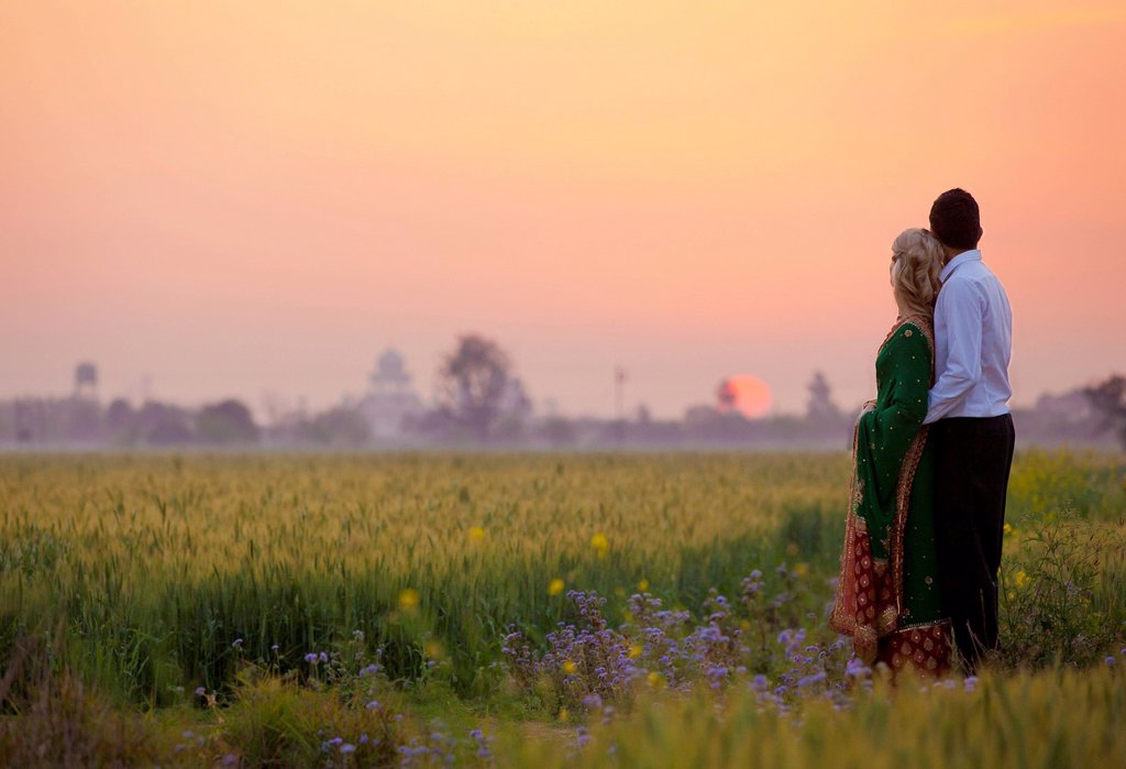 A couple standing together in a field at sunset, ludhiana punjab india : Stock Photo