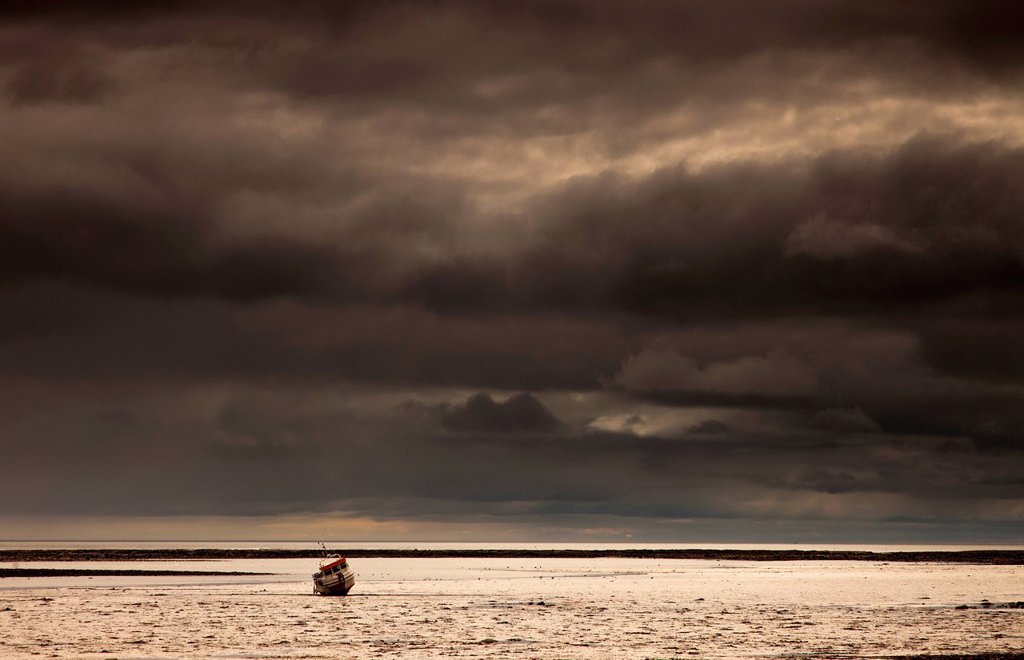 Stock Photo: 1889R-79097 A fishing boat out in the water under dark storm clouds, boulmer northumberland england