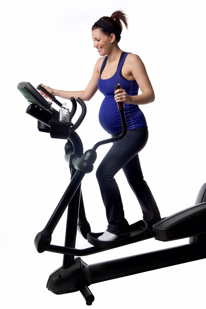 Stock Photo: 1889R-79186 A pregnant woman using fitness equipment, edmonton alberta canada