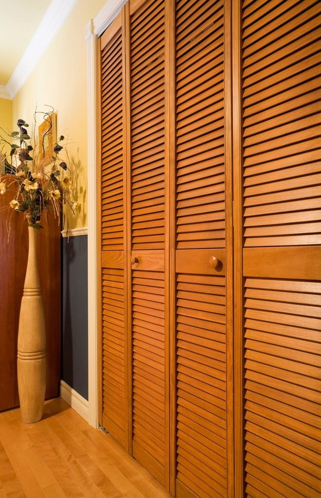 Stock Photo: 1889R-79196 Louvered panelled wooden closet doors in a bedroom, quebec canada