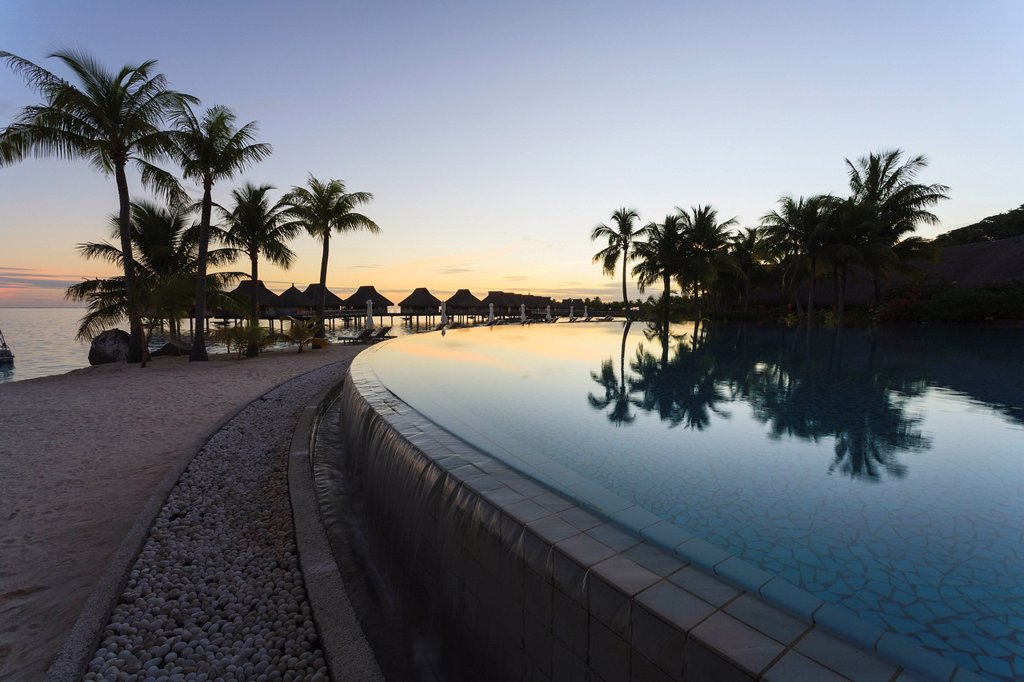 Sunset and palm trees reflecting in a pool at the bora bora nui resort and spa, bora bora island society islands french polynesia south pacific : Stock Photo