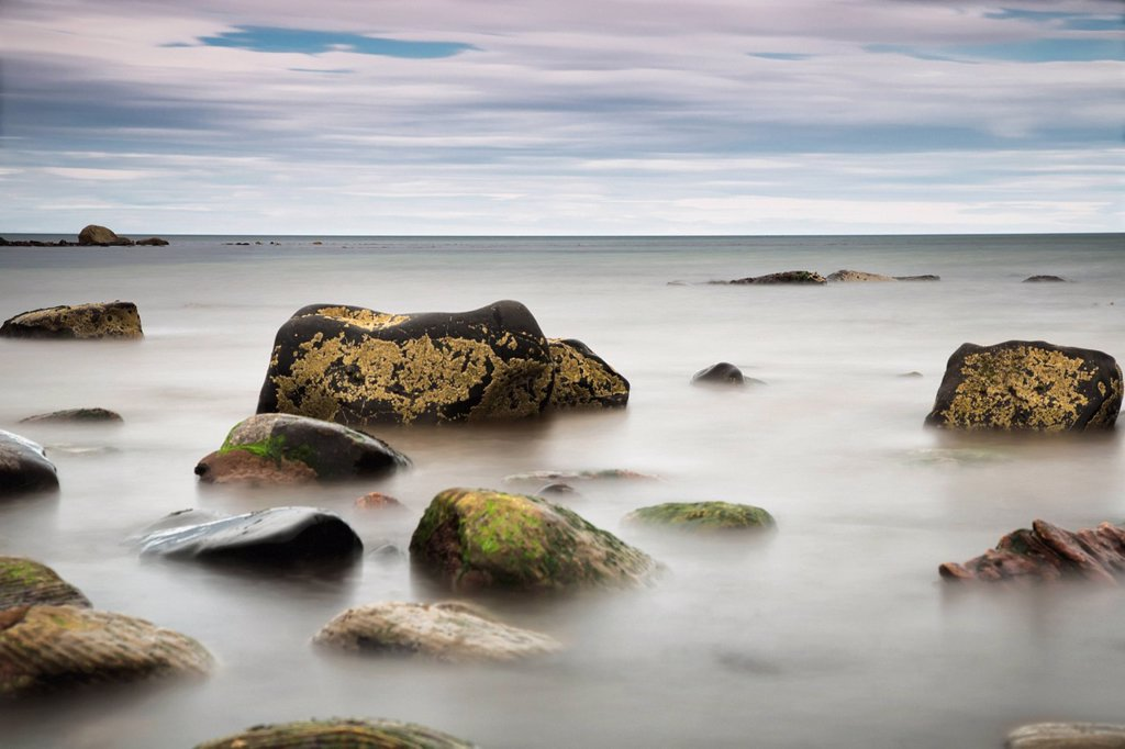 Large rocks sitting in the water : Stock Photo