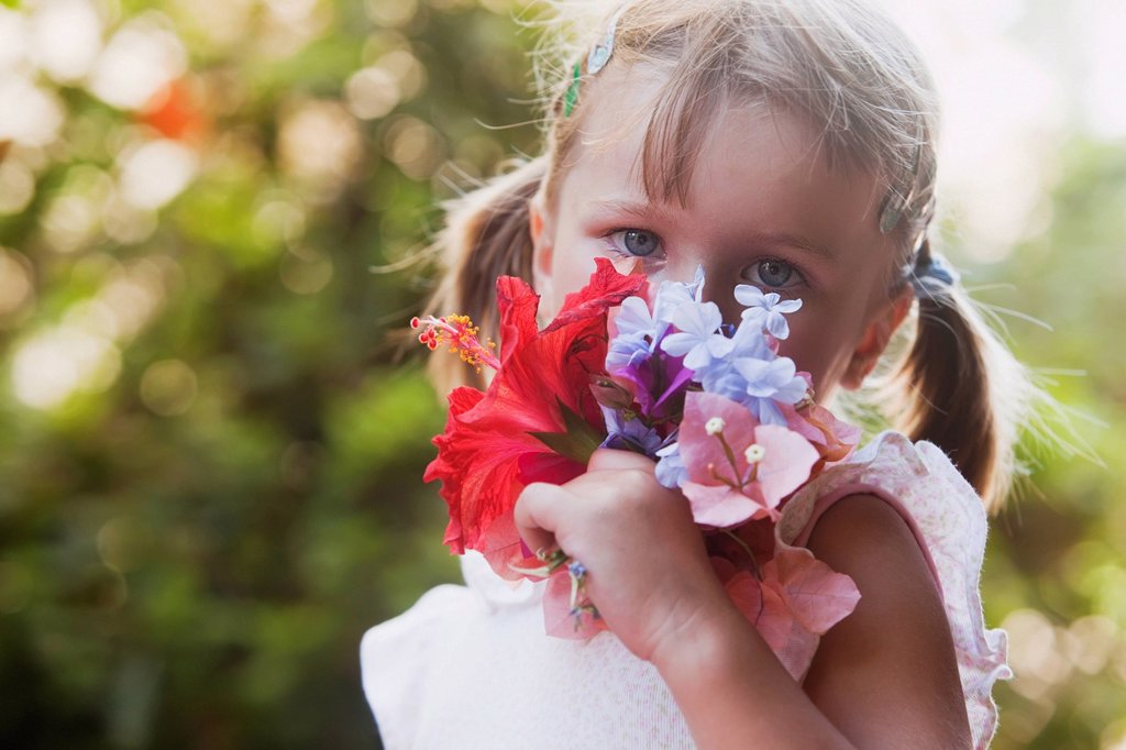 Stock Photo: 1889R-81925 A young girl smelling a colourful bouquet of flowers, torremolinos, malaga, spain