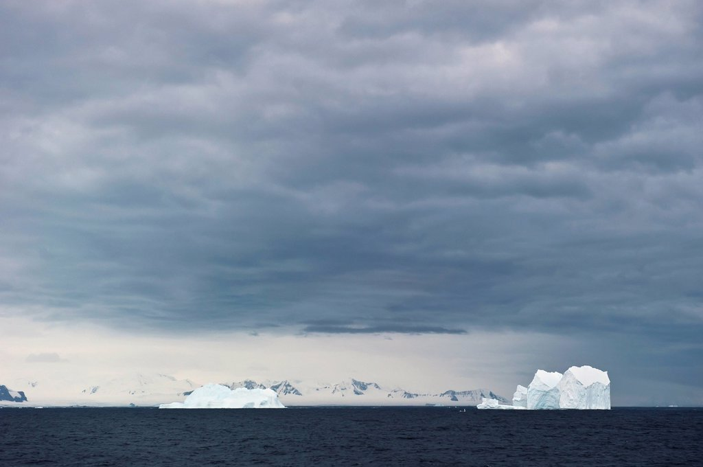 Icebergs under a cloudy sky, antarctica : Stock Photo