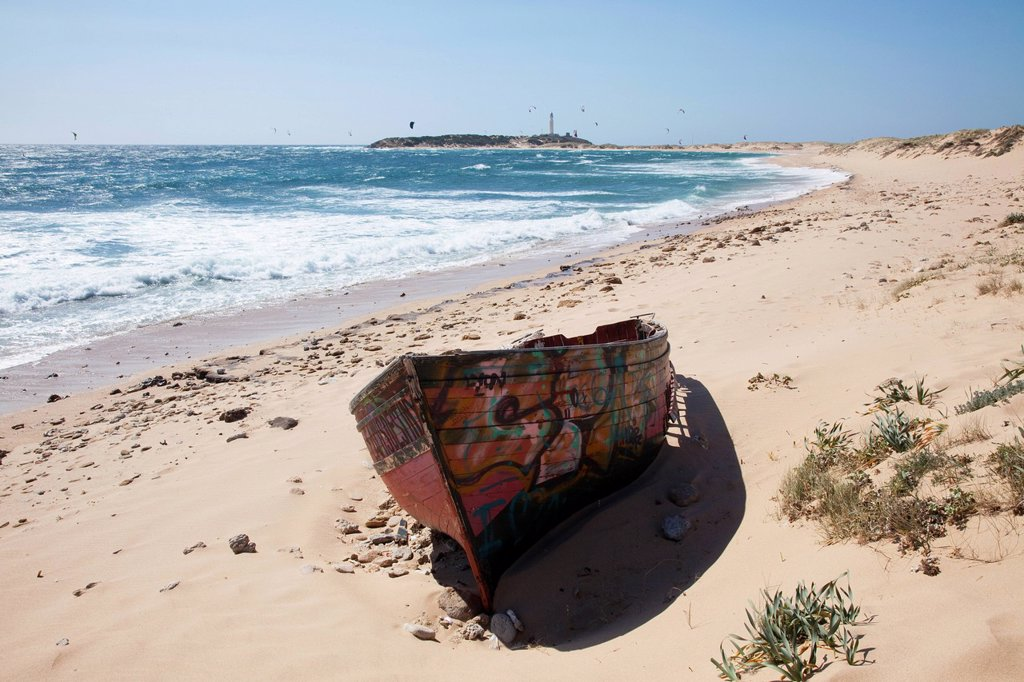 A painted wooden canoe sitting on a beach with the cape trafalgar lighthouse in the background, andalusia, spain : Stock Photo