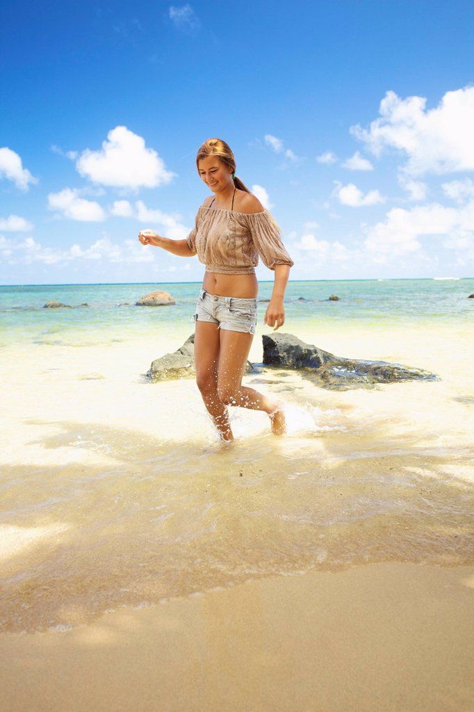 A young woman runs in the shallow water on anini beach, kauai hawaii united states of america : Stock Photo