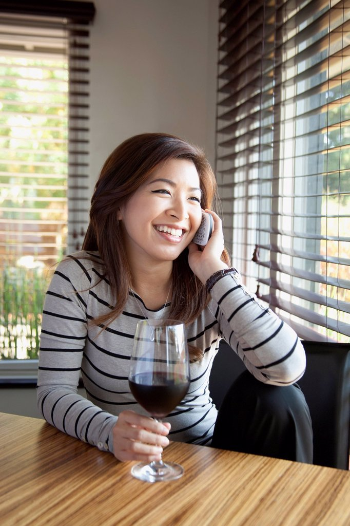 Stock Photo: 1889R-85175 A young woman talking on the phone while holding a glass of wine, berkeley california united states of america