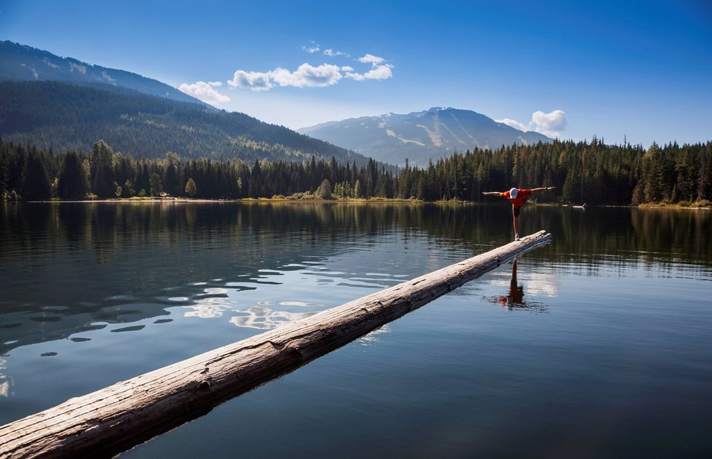 Stock Photo: 1889R-85193 A man practises yoga on a log boom in lost lake, whistler british columbia canada