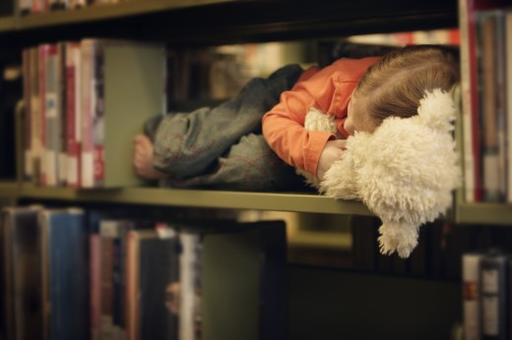 Stock Photo: 1889R-8761 Toddler falls asleep in a book shelf