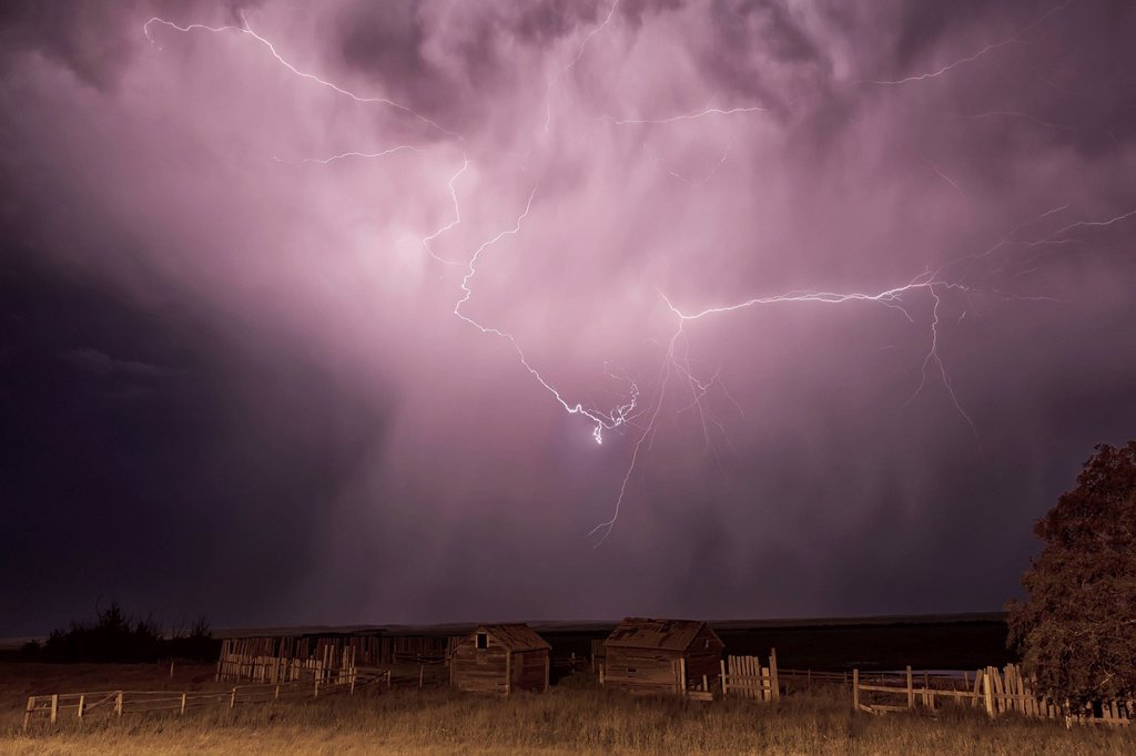 Lightning Bolt Over Some Abandoned Buildings Near Val Marie;Saskatchewan Canada : Stock Photo