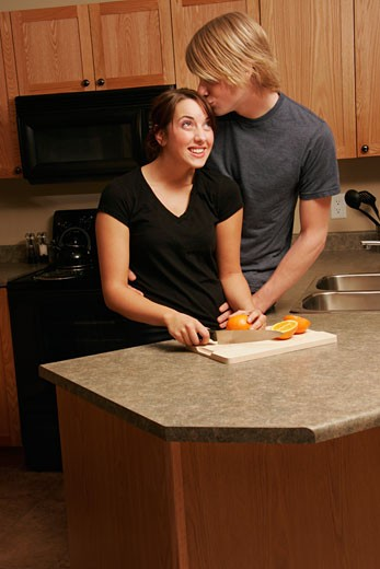 Stock Photo: 1889R-8779 Man kissing woman in kitchen