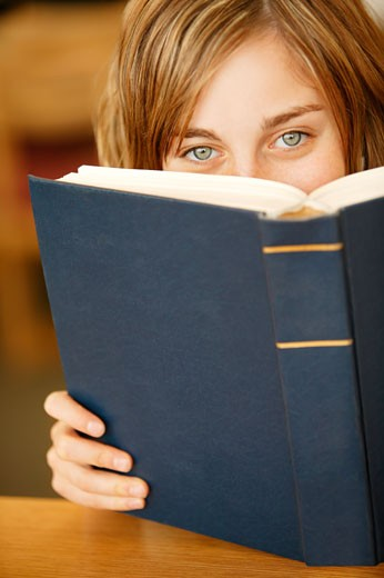Girl peering over the top of a book : Stock Photo