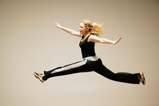 Woman leaps in the air : Stock Photo