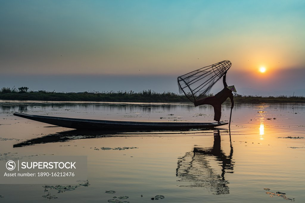 Stock Photo: 1890-16212476 Fisherman at Inle Lake with traditional Intha conical net at sunset, fishing net, leg rowing style, Intha people, Inle Lake, Shan state, Myanmar (Burma), Asia