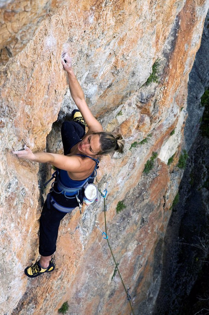 Stock Photo: 1890-101352 A climber makes her way up a steep and difficult route on the limestone cliffs in the Aveyron region, near Millau and Toulouse, south west France, Europe