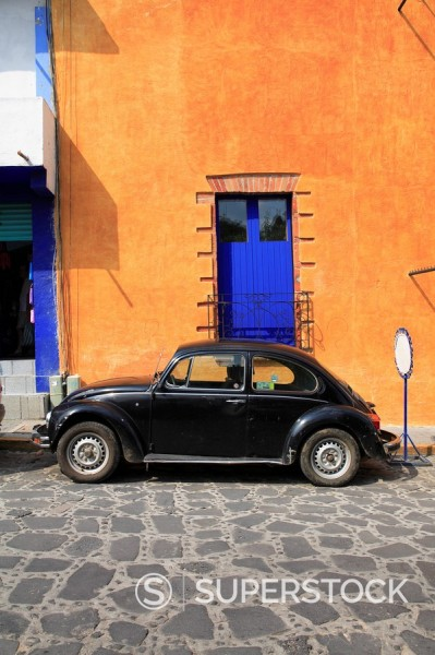 Stock Photo: 1890-101915 Volkswagon Beetle parked on cobblestone street, Tepoztlan, near Mexico City where many city dwellers spend weekends, Morelos, Mexico, North America