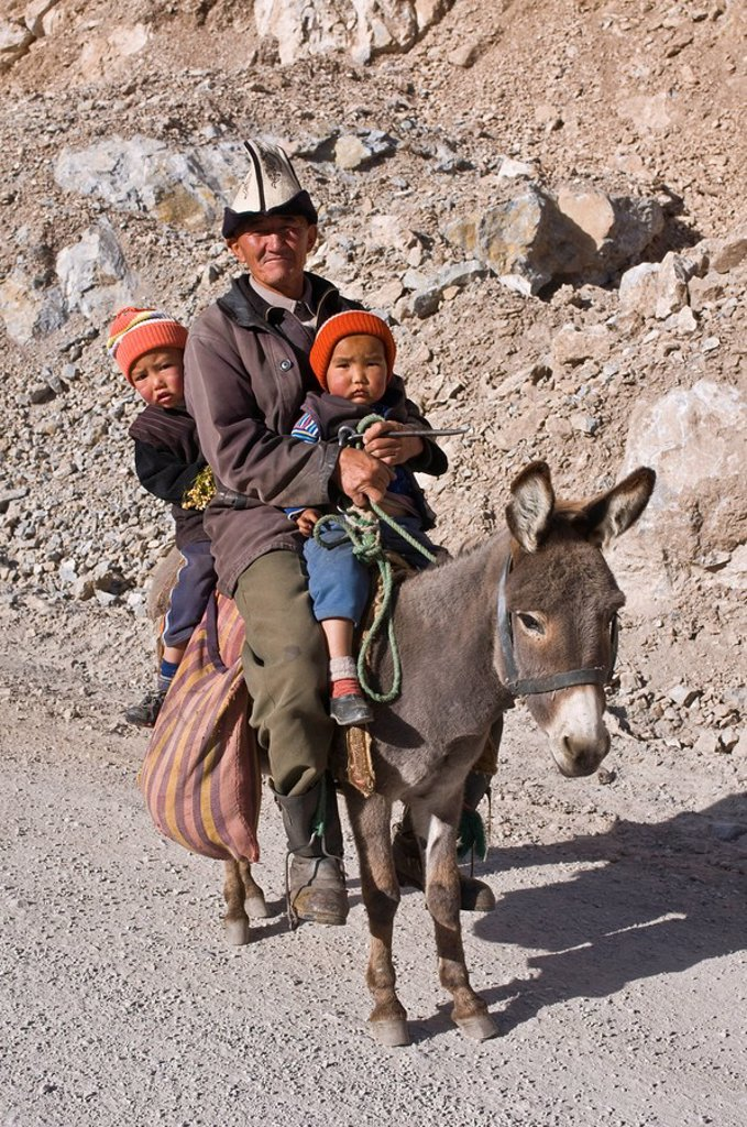 Stock Photo: 1890-104336 Old Kyrgyz man riding with twins on a donkey, Gulcha, Kyrgyzstan, Central Asia, Asia