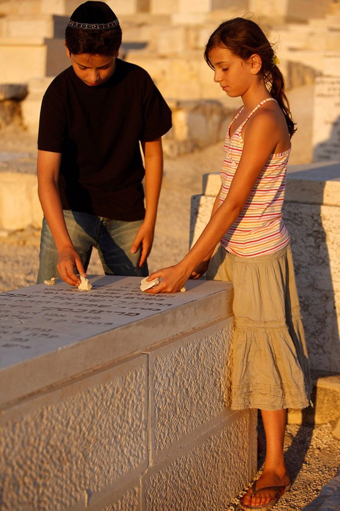 Brother and sister placing stones on a grave in the Mount of Olives Jewish cemetery, Jerusalem, Israel, Middle East : Stock Photo