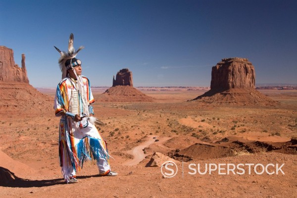 Stock Photo: 1890-110402 Navajo man dressed in traditional costume with Merrick Butte on the right and East Mitten Butte in the centre, Monument Valley Navajo Tribal Park, Arizona, United States of America, North America