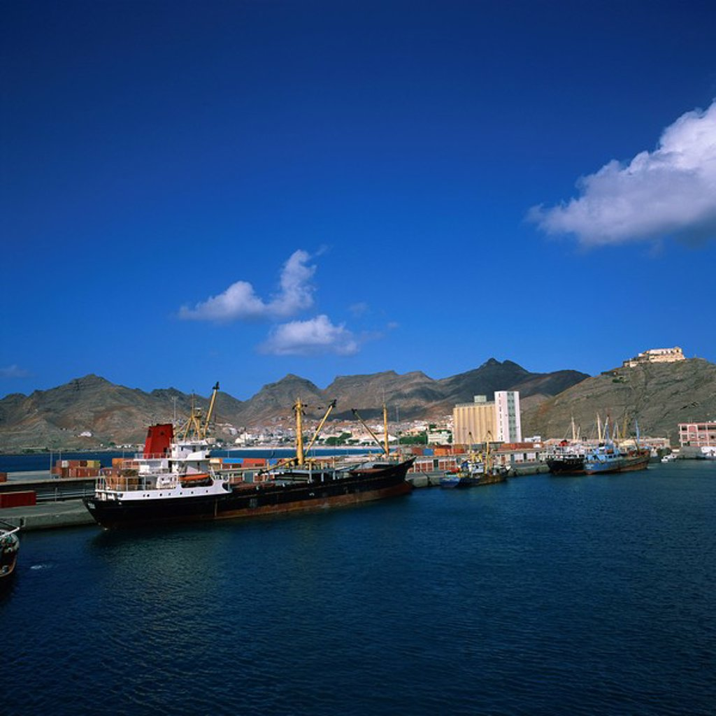Cargo ships in port, with the town and mountains in the background, Mindelo, Sao Vicente Island, in the Republic of the Cape Verde Islands, Atlantic, Africa : Stock Photo