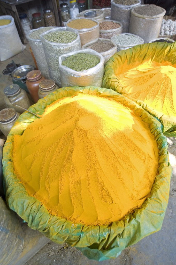 Spice market stall with large bowls of turmeric powder in early morning market on the banks of the Brahmaputra river, Guwahati, Assam, India, Asia : Stock Photo