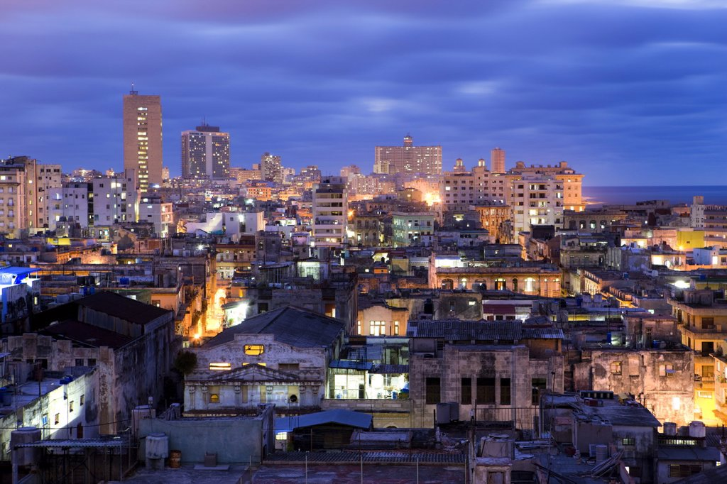 View over Havana Centro at night from Hotel Seville showing contrast of old, semi_derelict apartment buildings against a backdrop of more modern, affluent architecture, Havana, Cuba, West Indies, Central America : Stock Photo