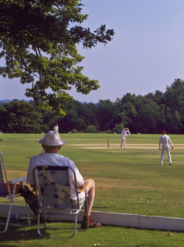 Stock Photo: 1890-116084 Man watching a game of cricket on Southborough Common, near Tunbridge Wells, Kent, England, United Kingdom, Europe