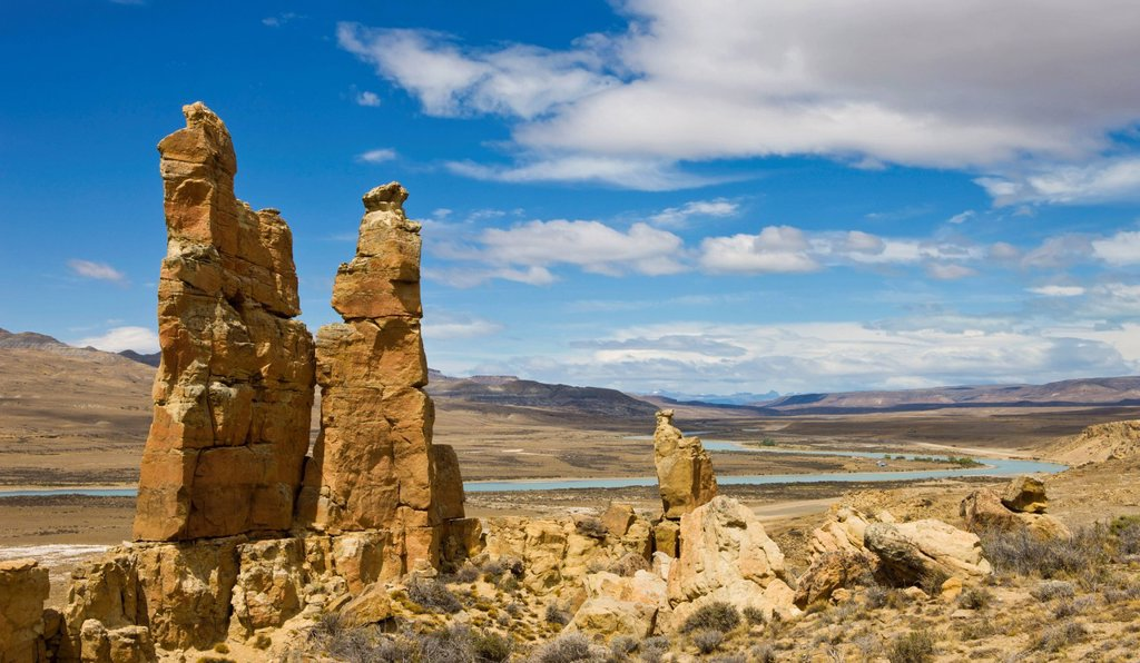 Pillars of weathered sandstone overlook River La Leona as it snakes through the Patagonian Steppe. La Leona, Patagonia, Argentina, South America : Stock Photo