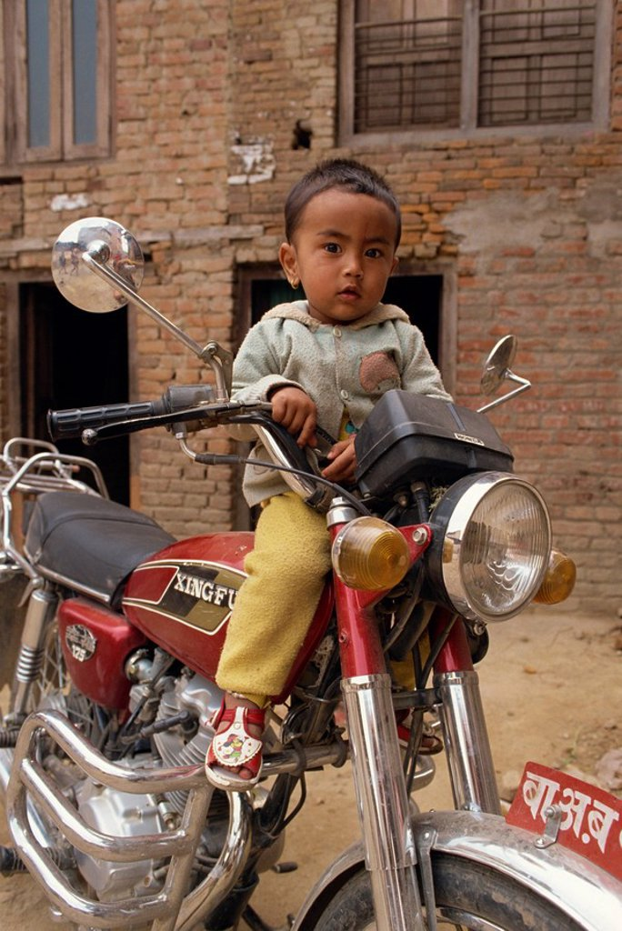 Stock Photo: 1890-12799 Portrait of young child sitting on motorcycle, Kathmandu, Nepal, Asia