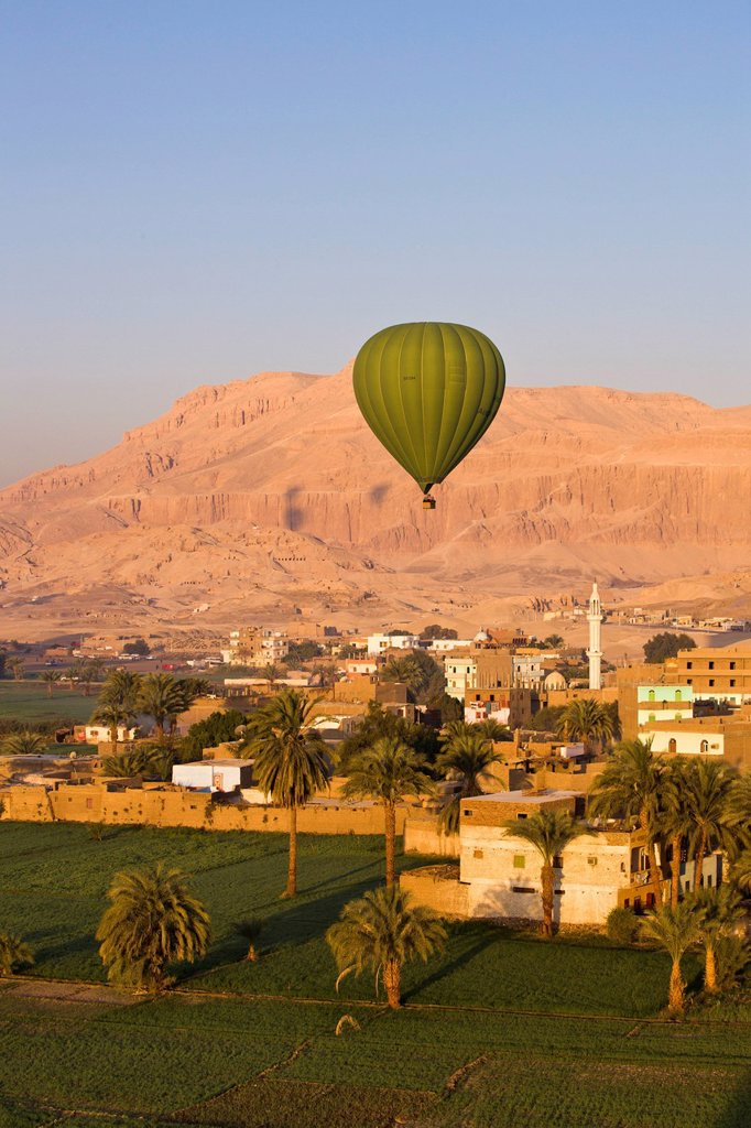 Hot air balloon suspended over the Theban necropolis and houses of Luxor, Thebes, Egypt, North Africa, Africa : Stock Photo