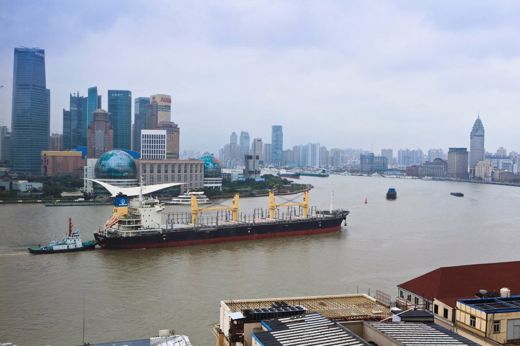 Large transport ship and tug on the Huangpu River that runs through Shanghai, China, Asia : Stock Photo