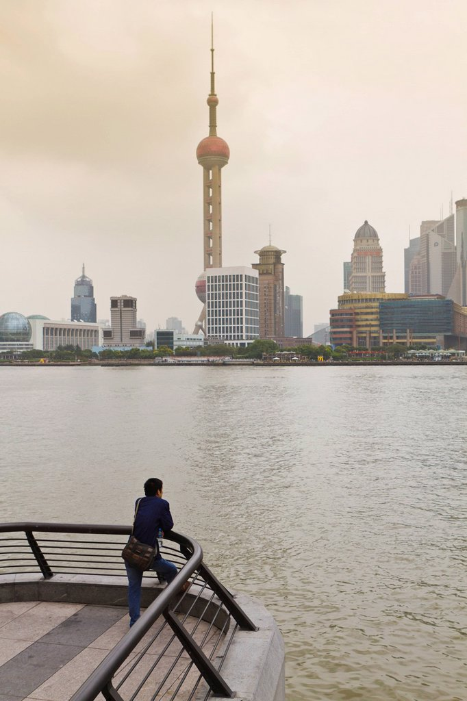 Stock Photo: 1890-131429 A man looking at the Oriental Pearl Tower and Pudong skyline across the Huangpu River from the Bund, Shanghai, China, Asia