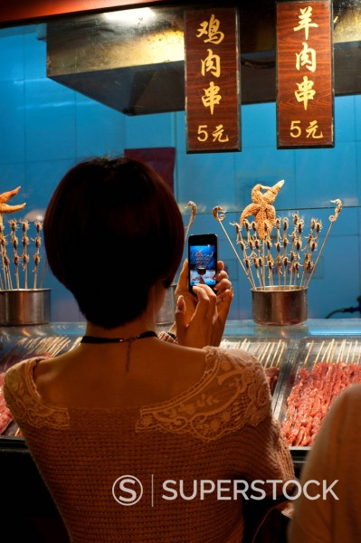 Woman using her iphone to take a picture of seahorses on a stick at Night Market Wangfujing, Beijing, China, Asia : Stock Photo