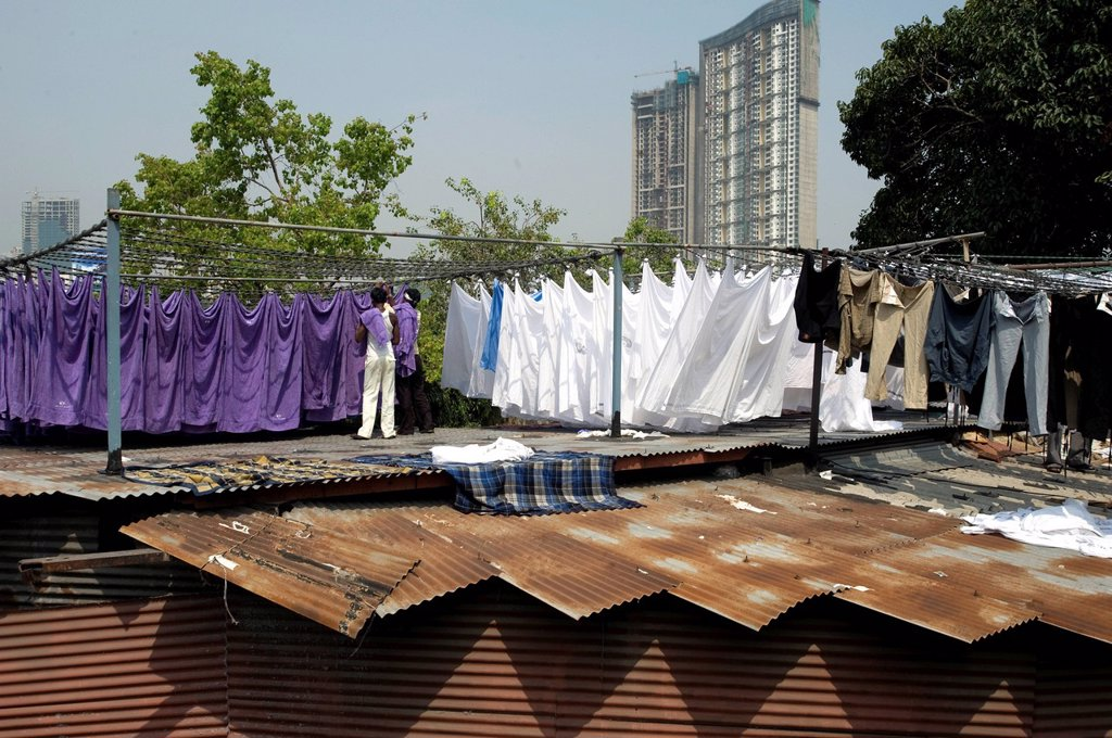 Laundrymen dhobi wallah, sorting laundry by colour on corrugated iron roofs, Mahalaxmi dhobi ghats, Mumbai, India, Asia : Stock Photo