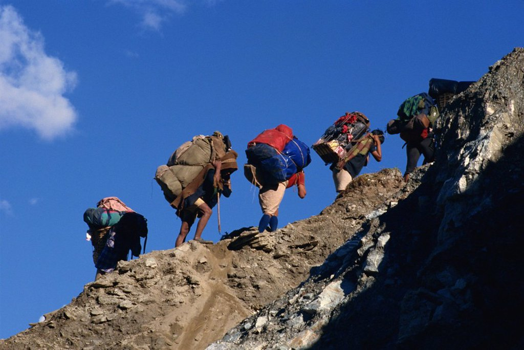 Stock Photo: 1890-14478 Trek porters on eroded trail to Ghorapani Pass near Chitre, Nepal, Asia