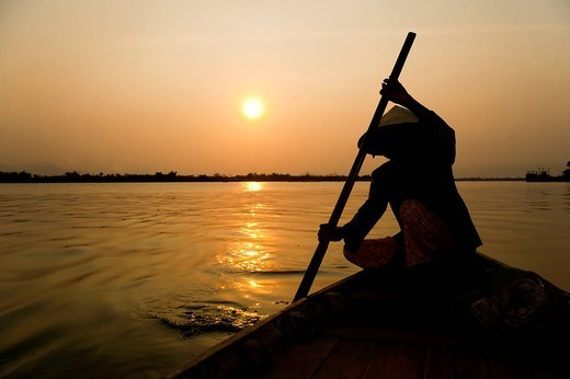 Old lady rowing in Hoi An harbour silhouetted at sunset, Vietnam, Indochina, Southeast Asia, Asia : Stock Photo