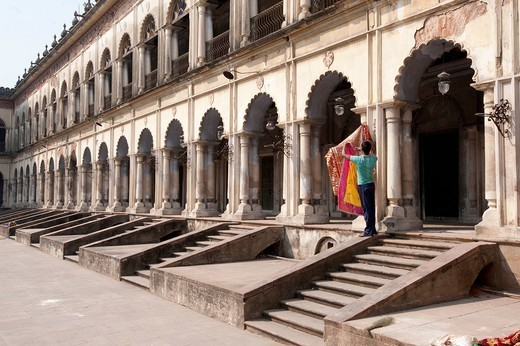 Man hanging out washed Quran cover cloths outside arched madrasa rooms in the Hugli Imambara, Hugli, West Bengal, India, Asia : Stock Photo