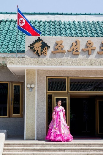 Stock Photo: 1890-149817 Woman in colourful traditional dress at entrance to tourist shop, Democratic People´s Republic of Korea DPRK, North Korea, Asia