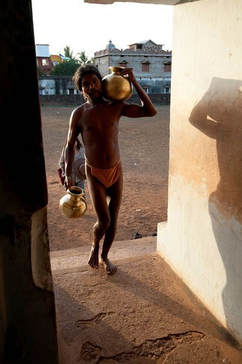 Monk, follower of Mahima Dharma sect, wearing orange loincloth carrying brass pots of water into the temple at sunset, Joranda, Orissa, India, Asia : Stock Photo