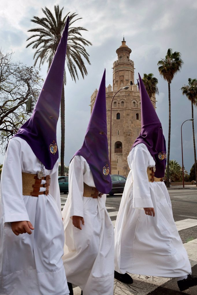 Stock Photo: 1890-156578 Penitents during Semana Santa (Holy Week) beneath Torre del Oro, Seville, Andalucia, Spain, Europe