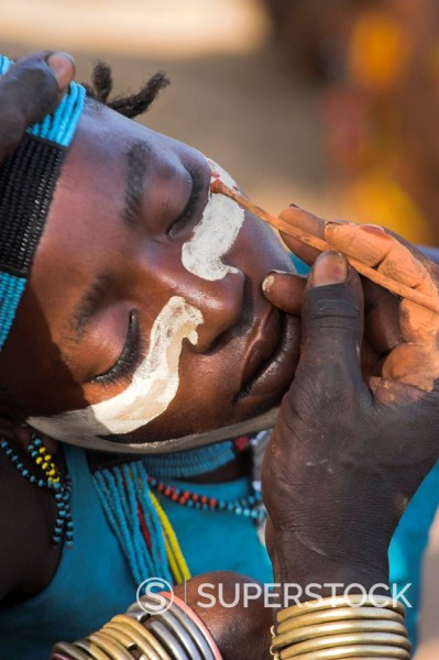 Face painting with a mixture of clay, oils and plant pigments in preparation for the Hamer Hamar jumping of the bulls initiation ceremony, Turmi, Lower Omo Valley, Ethiopia, Africa : Stock Photo