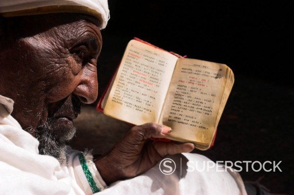 Old man wearing traditional gabi white shawl sitting in the sun reading holy bible, at church of Bet Medhane Alem Saviour of the World, Lalibela, World Heritage Site, Ethiopia, Africa : Stock Photo